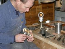 Photo of Jon Gibson restoring antique pewter